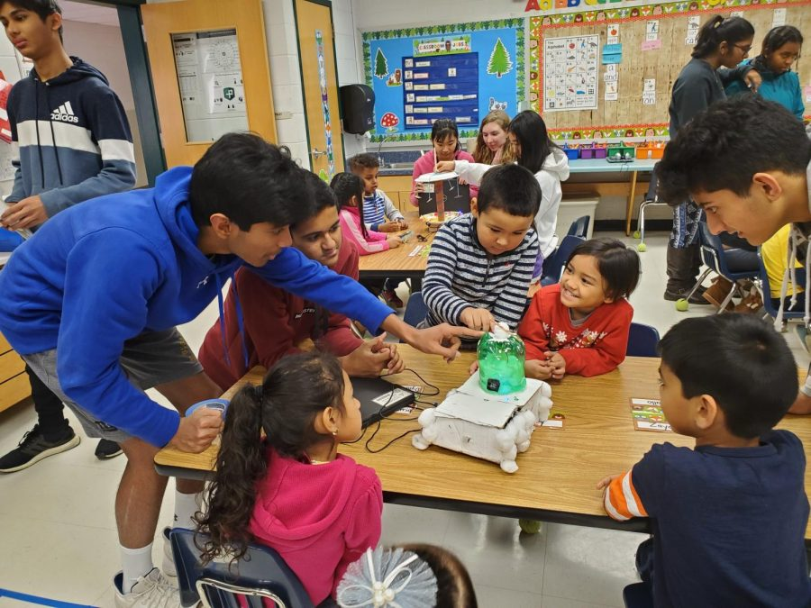 Freshman+Rusheel+Nadipally+and+freshman+Dhruv+Khatod+demonstrate+circuits+and+electrical+components+to+eager+elementary+school+students.