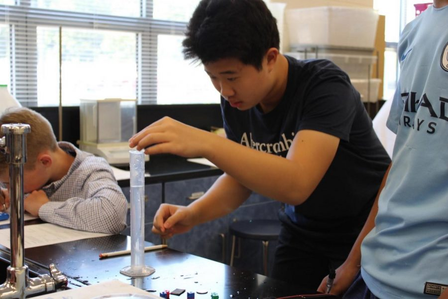 While+conducting+a+density+lab+in+chemistry%2C+sophomore+Bowen+Zhang+drops+an+object+into+a+graduated+cylinder+filled+with+water.