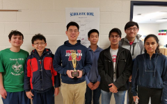 Following their victory at the regional scholastic bowl, the Quiz Bowl Team smiles with their trophy