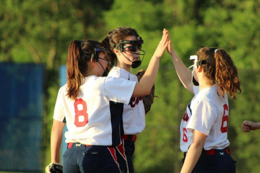 Girls on the 2019 softball team share a high five after a play.