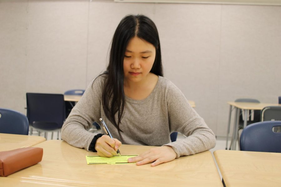 Writing a letter to her legislator, senior Jamie Lee engages in political activisim through her government class.