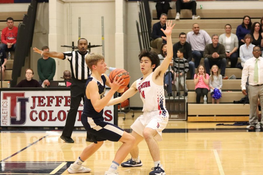 "Putting his hand out to block a shot, senior Samuel Kim defends against his opponent. The Varsity Men's Basketball team competed against the Trinity School at Meadowview on Friday night. ""I was forcing the ball to the right to my help defender. We call the defense '21' and it's a 1-3-1 concept,"" Huang said."