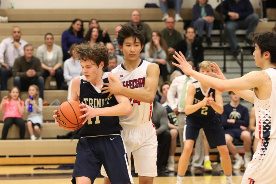 Senior+Alexander+Song+reaches+for+the+ball+to+transition+his+team+from+defense+to+offense.+On+Friday+night%2C+the+Men%E2%80%99s+Varsity+Basketball+team+played+the+Trinity+School+at+Meadowview.+A+grab+for+the+ball+from+behind+a+player+would+result+in+a+defensive+foul+against+Jefferson.