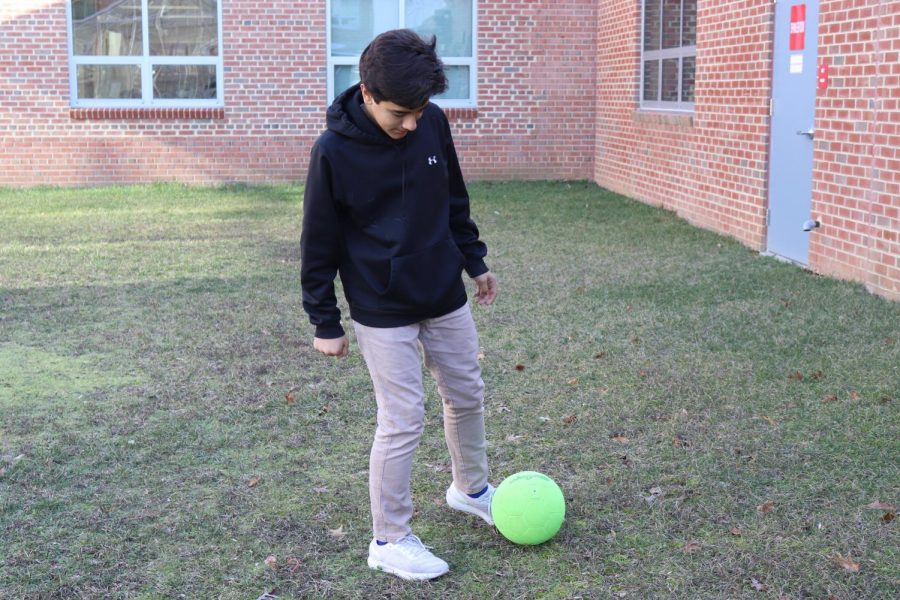 "Freshman Nicholas Artiedamarin practices around with a soccer ball. Soccer is a sport that relies heavily on teamwork and coordination, a characteristic that makes it enjoyable to many players. ""I feel like it's [soccer] a fun sport,"" freshman Rachit Ravali said, ""and it's interesting to play. You need to be able to work as a team player."""
