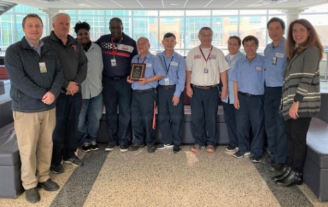 The custodian staff poses for a picture along with Dr. Bonitatibus, director of student activities Berkely hodges, and Manager of Plant Operations Andrew McCracken.
