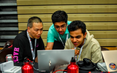 Jefferson CS instructor and HackTJ mentor Dan Tra watches as sophomores Harshavardhan Harish (left) and Umang Jain (right) run their code at the 2019 HackTJ 6.0.