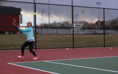 """Sophomore Yeefay Li prepares to return a ball. """"Tryouts were difficult because the weather was so unpredictable - for example, it was raining and snowing on Friday, so court conditions were really bad,"""" Li said."""