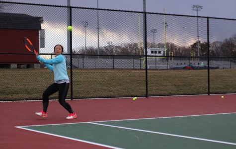 "Sophomore Yeefay Li prepares to return a ball. ""Tryouts were difficult because the weather was so unpredictable - for example, it was raining and snowing on Friday, so court conditions were really bad,"" Li said."