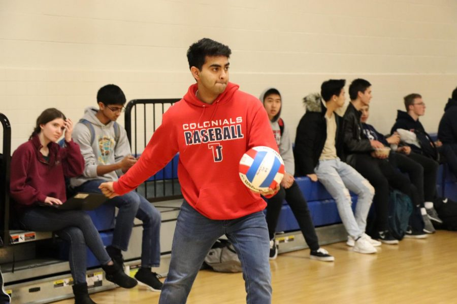 Arm held back, senior Saketh Gabbita prepares to serve the ball