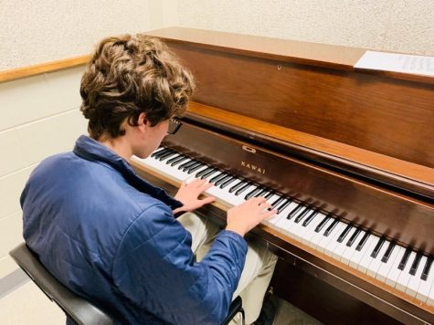 Pressing down on the piano keys, senior Robert Crotts improvs a slow melody