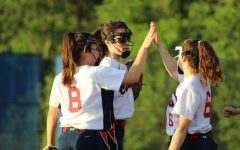 After preventing the runners on third and second from scoring additional runs on a sacrifice bunt attempt in the top of the third inning, junior Alexandra Friedman (right), graduated senior Grace Stewart (middle), and sophomore Michelle Boisvert (left) celebrate with a high-five before returning to their respective positions.