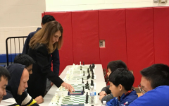 "Dr. Ann Bonitatibus makes the first move for senior Praveen Balakrishan, who placed first at the tournament. ""It is usually customary for a famous person to start off a chess tournament by making the ceremonial first move on the top board. As States was held at TJ, I was delighted when principal Dr. Bonitatibus made the first move for me at the beginning of the tournament."" Balakrishnan said."