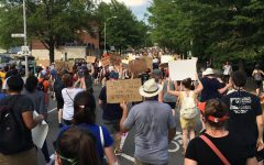 Protesters stand together at a protest in Arlington, holding up signs and marching peacefully.