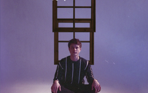 Released on May 29, Alec Benjamin's sits in front of two windows for the cover his debut album