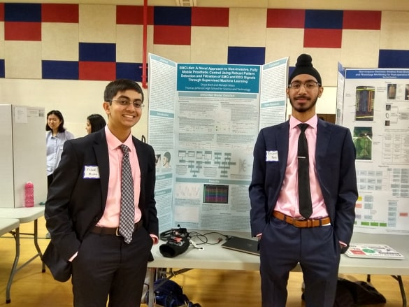 Smiling, juniors Divjot Bedi and Rishabh Misra stand by their science fair board