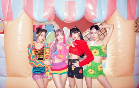 """Blackpink poses in front of a bouncy house in a promotional image for """"The Album."""" From left to right are the members, Jisoo, Jennie, Lisa, and Rosé."""