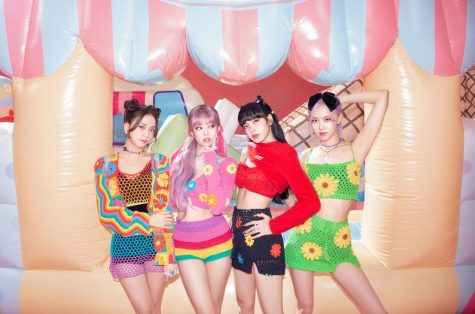 "Blackpink poses in front of a bouncy house in a promotional image for ""The Album."" From left to right are the members, Jisoo, Jennie, Lisa, and Rosé."