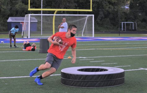 "Weaving his way around obstacles, junior Hilal Hussain participates in a running back drill. Players are now allowed to use footballs, but they must be disinfected regularly. ""It [felt] like a normal practice, which was a nice refresher from all the quarantine,"" Hussain said."