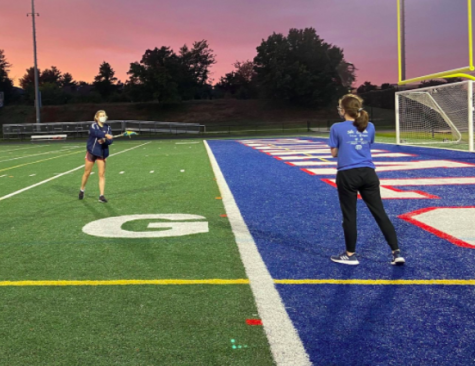 "In the midst of a passing drill, seniors Zoe Winston and Anais Beauvais practice lacrosse on the TJ field. Many aspects of usual lacrosse practices have been modified or cut to conform to safety guidelines. ""Obviously, we can't do contact drills anymore,"" Granum said. ""We can't be near each other and we wear masks all the time."""