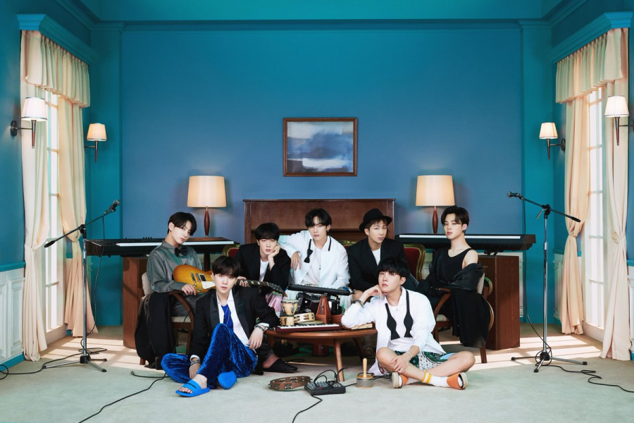 "BTS' album concept photo showcases the homely and uniquely ""them"" ambience of the album, with the bright but cool-toned colors, the symmetry of the room decor, and the asymmetry of the members. From left to right: Jungkook, Suga, Jin, V, RM, J-Hope, Jimin."