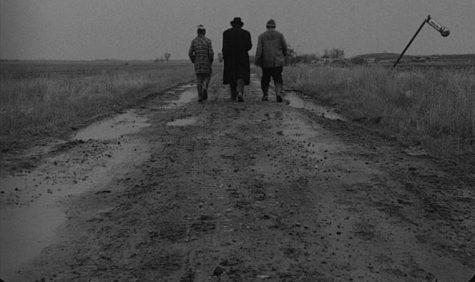 "Sanyi (András Bodnár), Irimiás (Mihály Víg), and Petrina (Putyi Horváth) walking down one of many endless muddy roads in ""Sátántangó"". Image courtesy of Filmgrab."