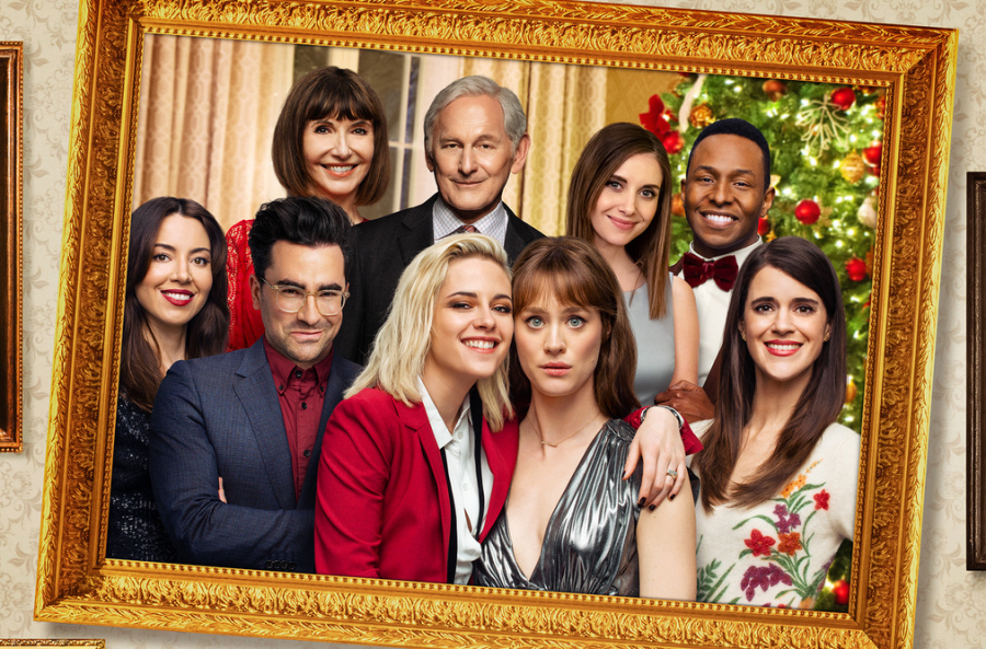 "The cast of ""Happiest Season"" in front of a Christmas tree, with the stars Kristen Stewart and Mackenzie Davis in the very front."