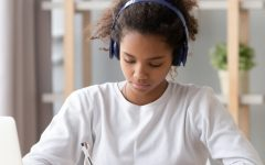 A girl takes notes while listening to music, effectively remaining focused on her current task. This use of audio stimuli for concentration is a typical depiction of the modern student.