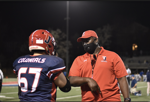 Offensive lineman Oliver Tu (67) receives advice from offensive line coordinator Enoch Boateng.