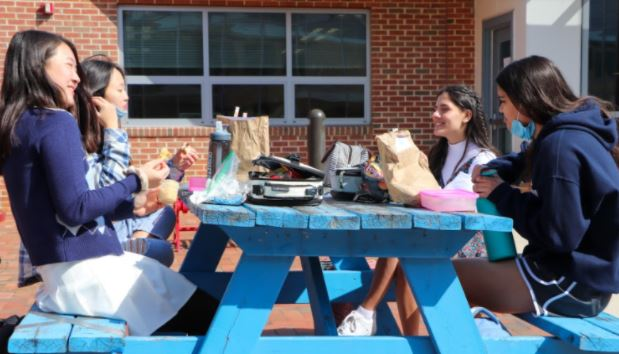 "Students eat lunch outside in the Nobel courtyard. On March 4, freshman and seniors last names L-Z returned to school amid the Coronavirus pandemic. ""We never lost sight of keeping students, quality instruction, and wellness as our focus."" Jefferson Principal Dr. Bonitatibus said."