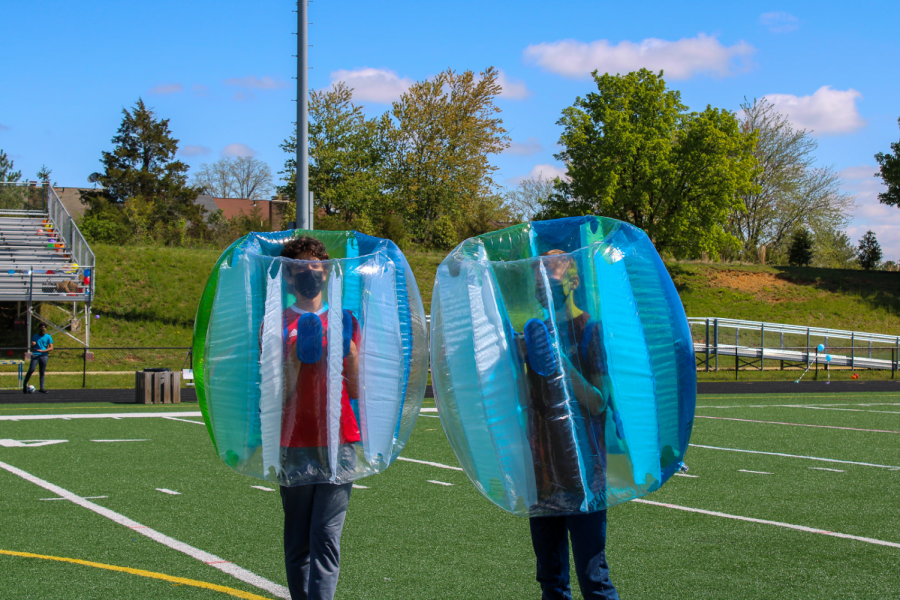 """Prepping for their bubble soccer match, freshmen Ethan King and Santiago Criado get ready to go against the seniors, and subsequently, the juniors. Bubble soccer was a new event added this year, where players aim to score a soccer goal while being able to knock down opponents in their respective bubbles. """"It was so much fun to combine the skill and teamwork side of soccer with [inflatable] bubbles, it was definitely a new experience for me,"""" King said."""