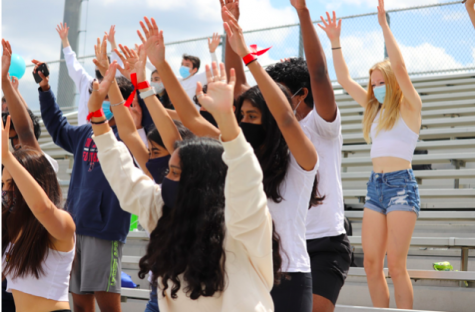 Students in the Class of 2023 cheer from the stands during one of TJ's 2021 pep rallies. At the pep rally, students upheld the tradition of wearing their signature class color.