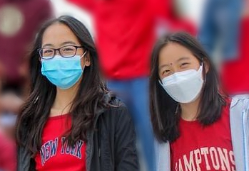 """From left to right, Lindsay and Ashley Hwang smile amongst their classmates on the freshmen bleacher stands during a homecoming pep rally. """"I love hanging out with Lindsay, especially when we're at a big event or something; it's really nice to have someone I know I can count on,"""" A. Hwang said."""