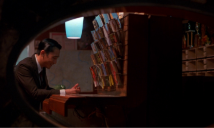 Mr. Chow (Tony Leung) is framed within a mirror and a wall to keep him trapped. Image courtesy of [FILMGRAB].