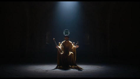 """Dev Patel's Gawain sits on a throne and has a crown lowered onto his head in the opening scene of """"The Green Knight""""."""