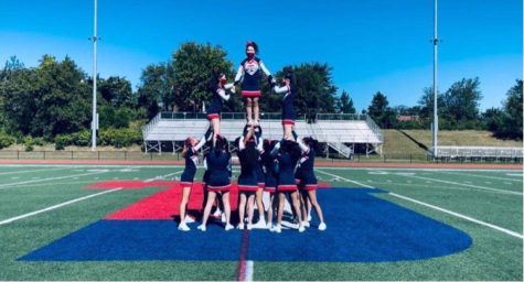 """The TJHSST cheer team practices together on the football field. """"I think the community of people who are in cheer is really fun and laid back, and everyone's super supportive,"""" senior Justine Chu said."""