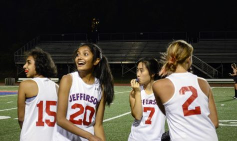 As the scoreboard changes from 0 to 1, Samhitha Singiresu (20) looks over with her fellow teammates, smiling.