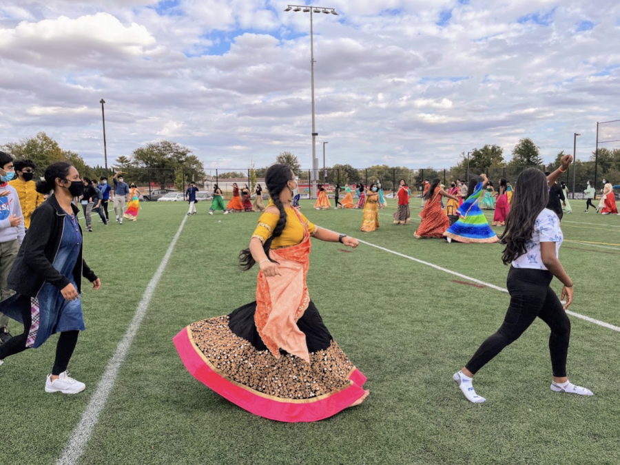 """Students wear Indian clothing and dance together in circles at Namaste's Garba celebration. """"I really liked the dancing since it was pretty chaotic. Sometimes people would be scrambling to get to the next move, but it was fine because you could lose yourself in the music. You really got to enjoy yourself since the movements were energetic,"""" sophomore Neha Asuri said."""
