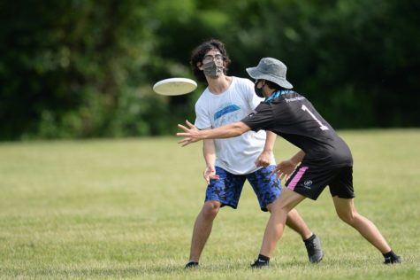 """At the 2021 Virginia High School State Competition, senior Kareem Jaber rifles the frisbee past a Marshall High School player. """"The main thing about [ultimate frisbee] is just having fun. There's not as much competition [as] there [is] sometimes in football or other sports,"""" Jaber said."""